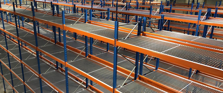 Auf den Traversen des Regals wurden Gitterroste befestigt, damit man auch andere Waren, die nicht auf Paletten gelagert sind dort einlagern kann