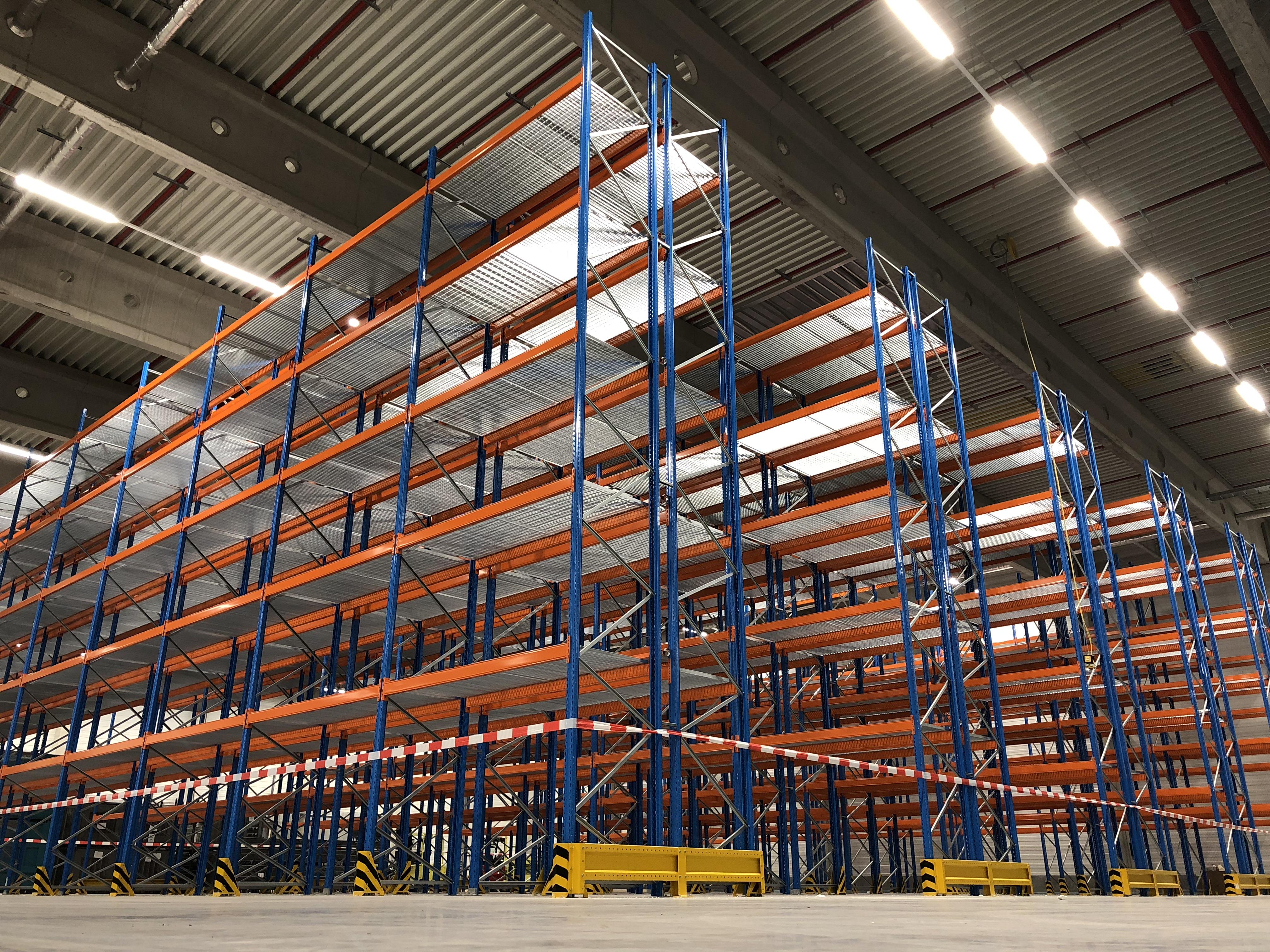 Das orange-blaue Palettenregal von Stow steht kurz vor der Montage bzw. dem Service. Die Lagertechnik muss geprüft werden. Nach der Regalprüfung werden kaputte Bestandteile des Regals durch Neue ersetzt.